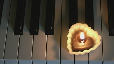Heart-shaped candle on a piano