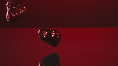 Heart shiny shapes falling and bouncing