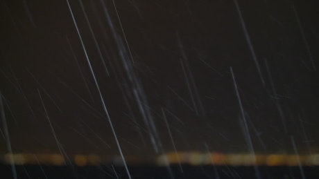 Heavy rain over the ocean at night