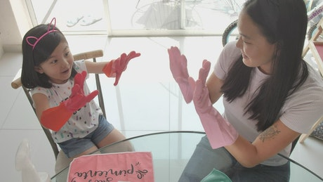 Hi-five between mother and daughter for cleaning their house