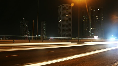 Highway at night with cars and buildings, exposure