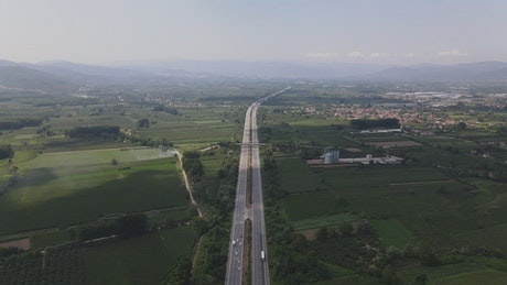 Highway between large green fields from very high