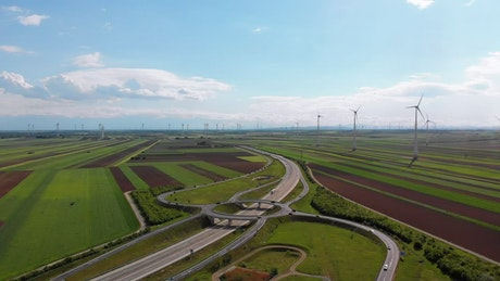Highway traffic and a wind farm in the countryside
