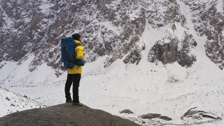 Hiker with a backpack watching the winter mountains