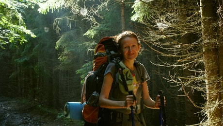 Hiker woman with big backpack in the forest