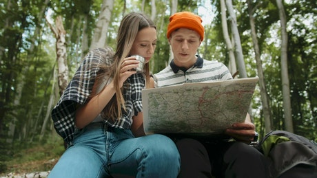 Hiking couple resting and looking at map