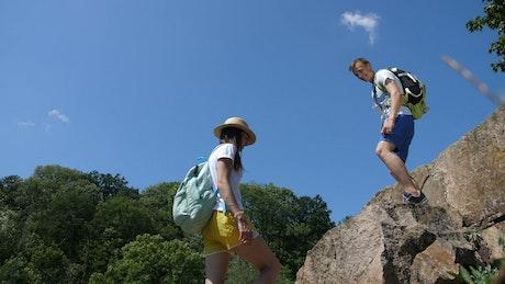 Hiking man helping his partner climb