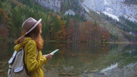 Hiking woman looking at map at the lake shore
