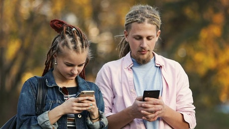 Hip urban couple surf internet on mobile phones outside in autumn
