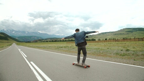 Hipster man on a longboard on the road
