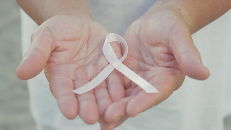 Holding a Breast Cancer ribbon in her hands