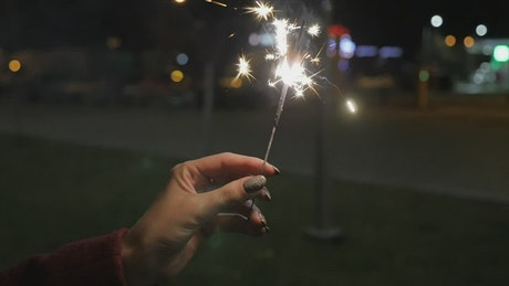 Holding a sparkler at night