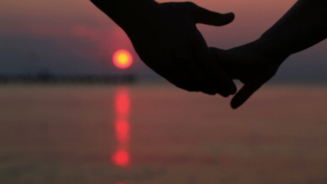 Holding hands during a dark sunset