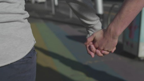 Holding hands over rainbow crosswalk