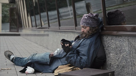 Homeless man checking the mobile phone on the sidewalk