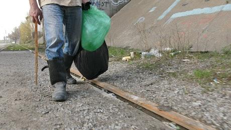 Homeless man collecting bottles