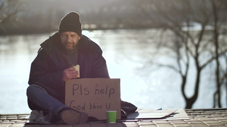 Homeless man eating and begging on the street