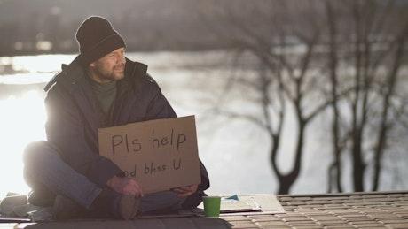 Homeless man putting away money