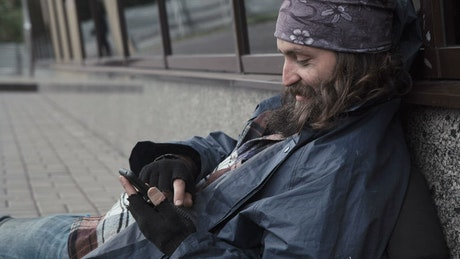 Homeless man scrolling on his phone