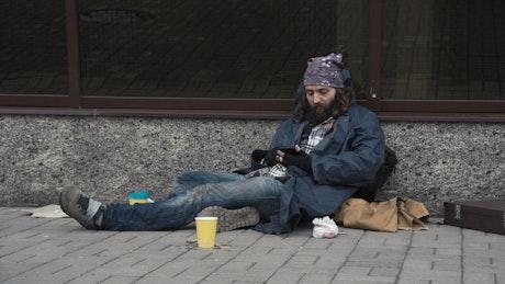 Homeless man using smartphone on the street