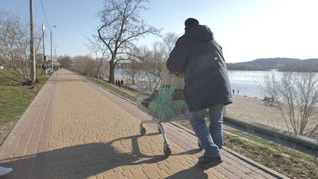 Homeless man walking by the lake