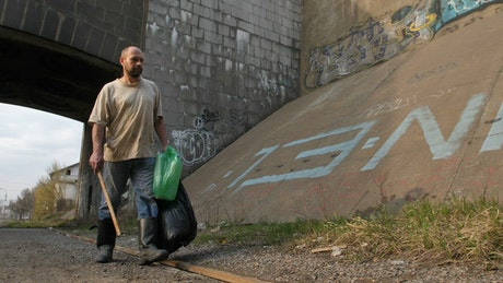 Homeless man walking with bags