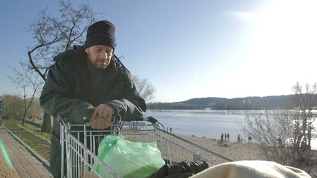 Homeless man with a cart of plastic bags
