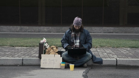 Homeless man with a laptop sitting on the sidewalk