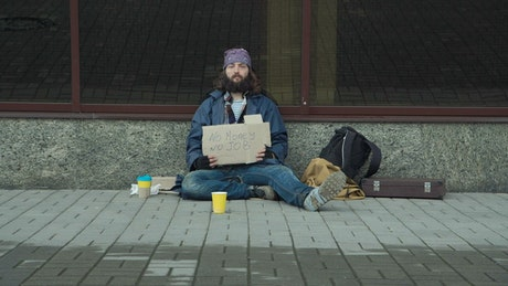 Homeless with cardboard sign sitting on the street