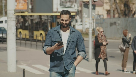 Hopeful man smiles at social media while walking through city
