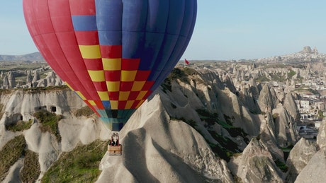 Hot air balloon floats over Turkish landscape