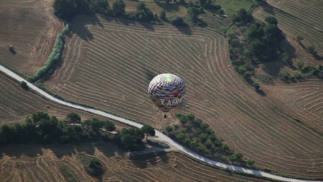 Hot air balloon flying over the fields
