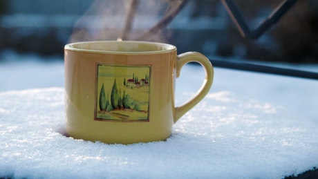 Hot beverage over a snowy surface