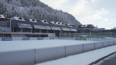 Hotel in the mountains with sports field covered in snow
