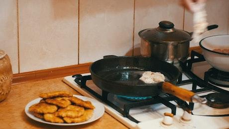 Housewife frying meat in a frying pan