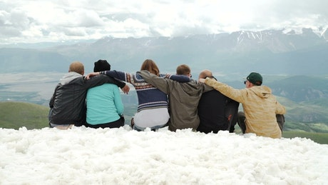 Hugging friends look at mountain landscape from snowy ridge