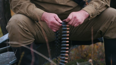 Hunter loading a belt of bullets in a nearby shot