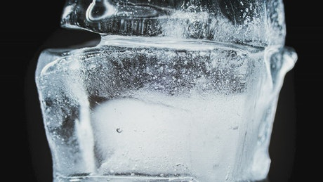 Ice cubes thawing on black background