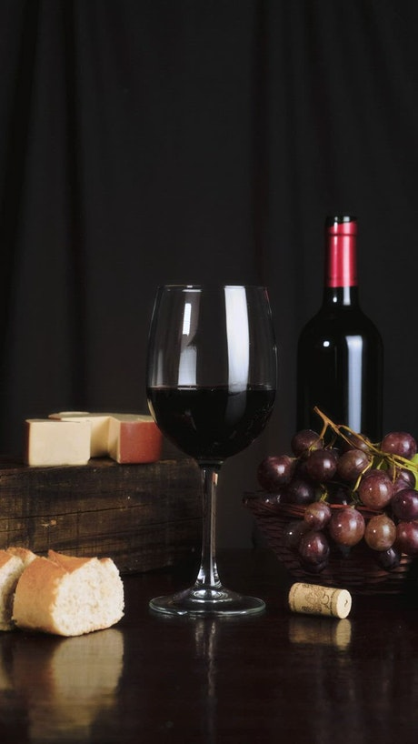 Image composition on a table with wine, cheese, grapes and bread