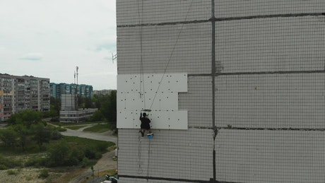 Industrial alpinist painting a wall