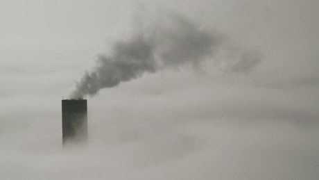 Industrial chimneys above the clouds and environmental pollution