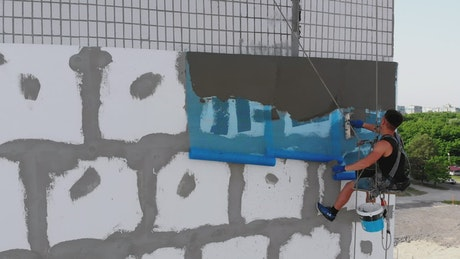 Industrial climber putting cement to a wall