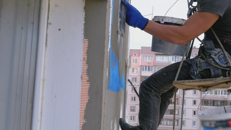 Industrial climbers applying cement to a building