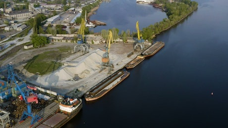 Industrial cranes and cargo ships by the river