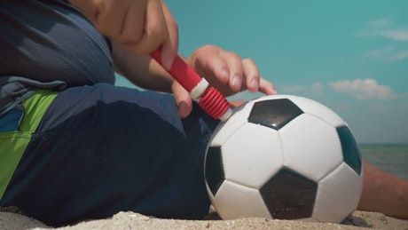 Inflating a ball at the beach