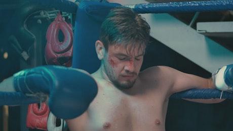 Injured boxer sitting in the ring