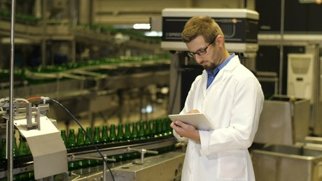 Inspector checking production of beer bottles