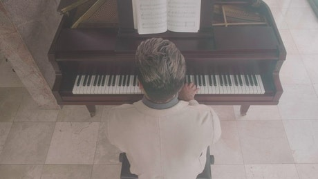 Inspired male pianist playing a grand piano