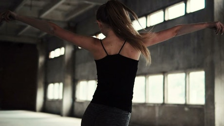 Inspired woman dances in warehouse