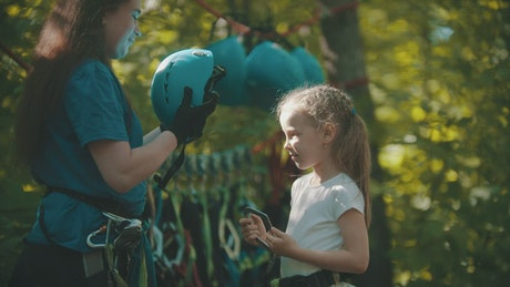 Instructor putting a protective helmet on a little girl